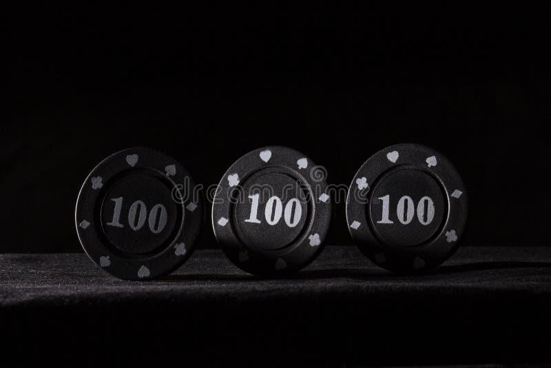 Tre svarta pokerchiper på en mörk bakgrund royaltyfria bilder