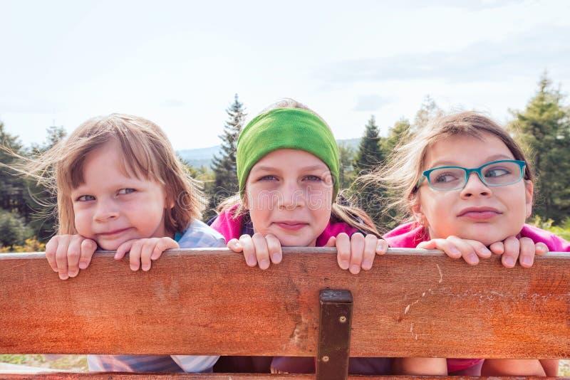 Tre systrar på en bergtur som döljer bak ett staket - skog och berg i bakgrunden bak dem royaltyfria foton