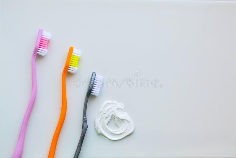 Tre tandborstar på en vit bakgrund och en vit tandkräm Begreppet av tand- hygien, personlig omsorg arkivfoton