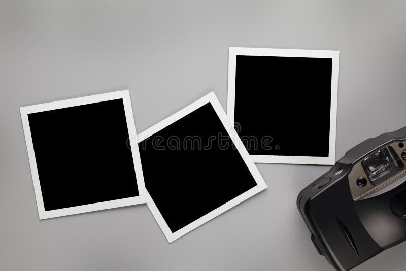 Tre tappningfotoramar med tomt utrymme för ditt innehåll och den gamla fotokameran på den gråa tabellen arkivfoton
