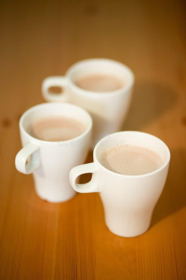 Tre tazze di caffè, cacao o latte bianchi su un fondo di legno sulla tavola, primo piano fotografie stock