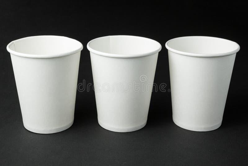 Tre tazze di carta beventi del caffè per tè, caffè e succo caldi su fondo nero, modello fotografie stock