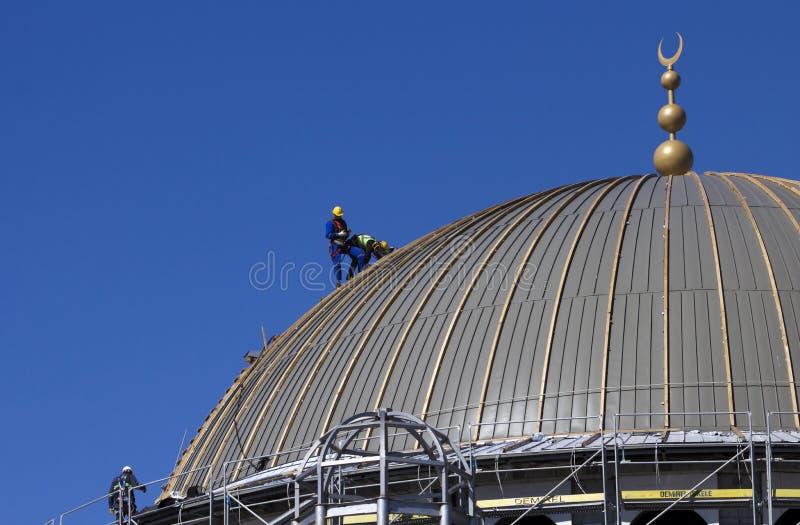 Tre tekniker kontrollerar kupolen av den Taksim moskén under konstruktion royaltyfria foton