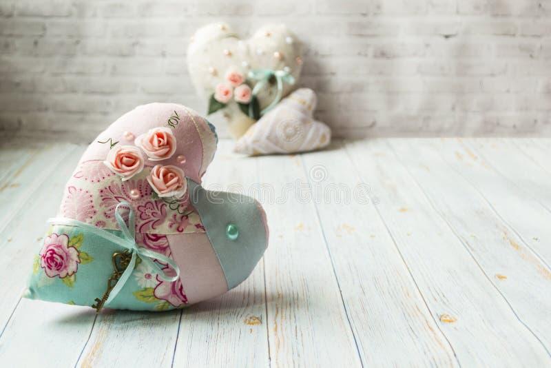Tre textilhj?rtor med en romantisk blommaf?rg p? en enkel ljus tr?bakgrund Selektivt fokusera Det finns ett st?lle f?r text arkivfoton