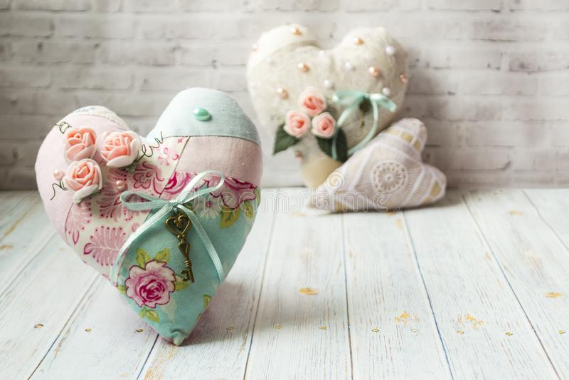 Tre textilhj?rtor med en romantisk blommaf?rg p? en enkel ljus tr?bakgrund Selektivt fokusera Det finns ett st?lle f?r text royaltyfri fotografi