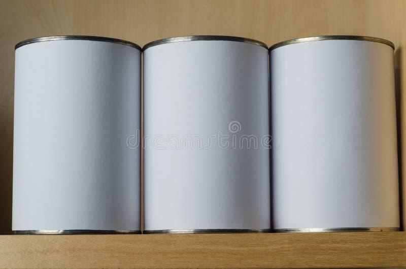 Tre Tin Cans On Shelf med tomma vita etiketter royaltyfri bild