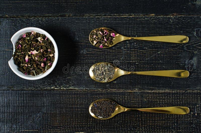 Tre tipi di tè in cucchiai - verdi, nel nero e in Rooibos immagine stock libera da diritti