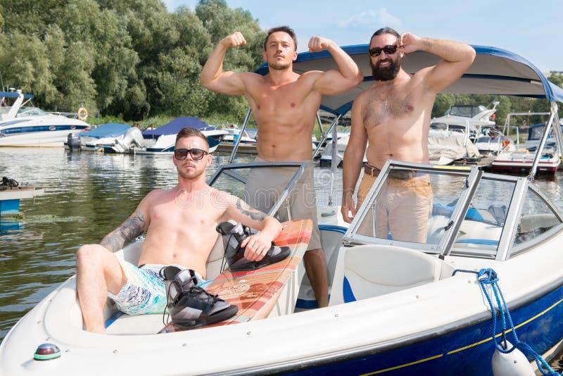 Tre tipi stanno su una barca sulla sponda del fiume fotografia stock