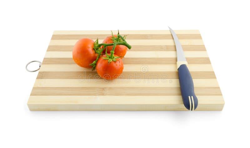 Tre tomater på den gröna filialen på skrivbordet med kniven arkivfoto