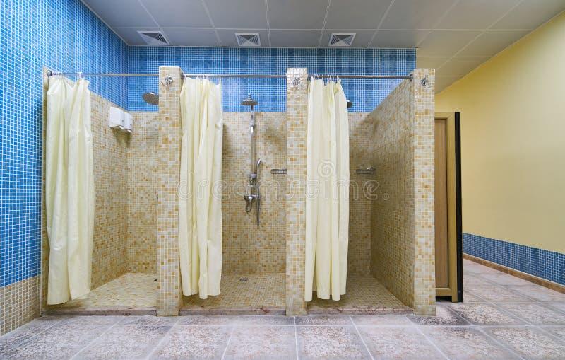 Tre tomma duschar i modern idrottshall royaltyfri foto