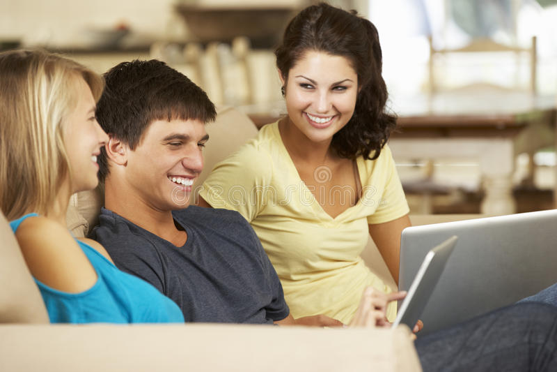 Tre tonåringar som sitter på den Sofa At Home Using Tablet datoren och bärbara datorn arkivbild