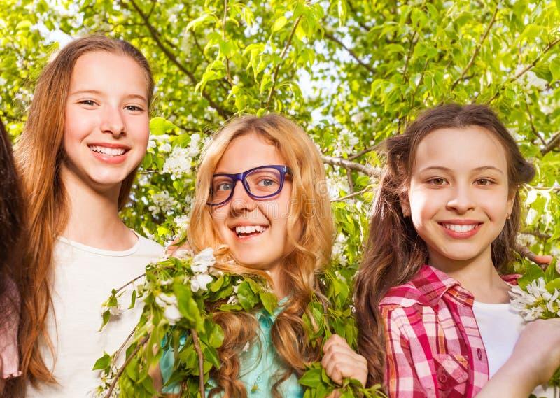 Tre tonårs- flickor som rymmer bänkar av trädet fotografering för bildbyråer