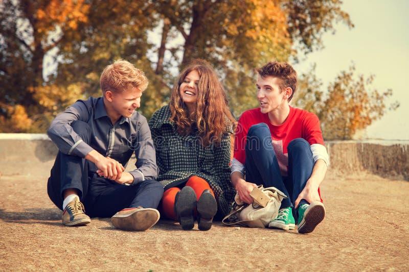 Tre tonårs- vänner har en rolig tid i guld- höstdag arkivbilder