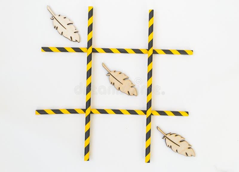 Tre träfågelfjädrar ställs upp i en rastermuskelryckning-TAC-tå lek på en vit bakgrund Rastret best?r av kul?ra r?r fr?n arkivfoton