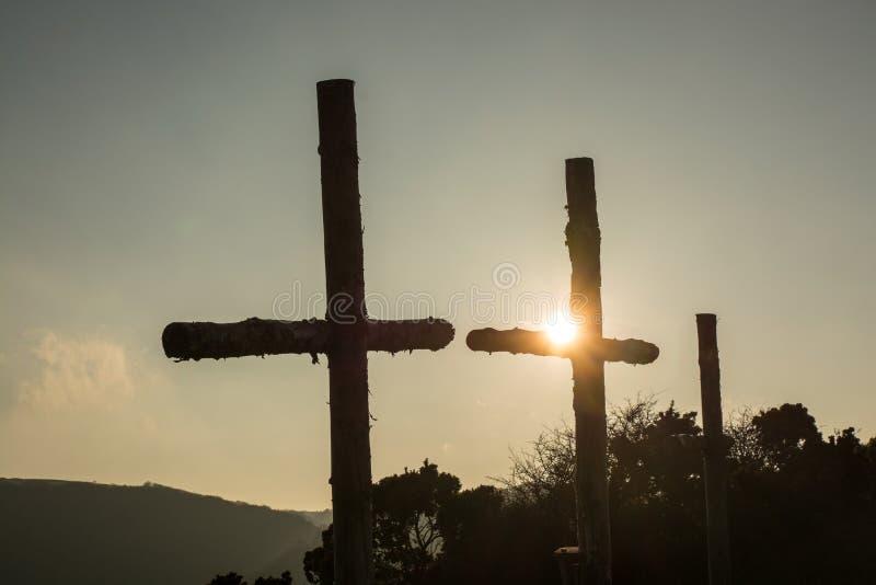 Tre träkors i solnedgång arkivfoton