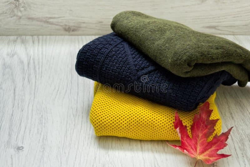 Tre tröjor och en lönnlöv på en träbakgrund trendigt begrepp arkivbilder