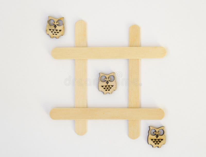 Tre tr?ugglor ligger i rad i en linje i leken av muskelryckning-TAC-t?n, i ett raster p? en vit bakgrund royaltyfri bild