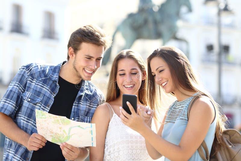 Tre turist- vänner som konsulterar gps på den smarta telefonen royaltyfri fotografi