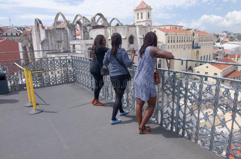 Tre turister i den Lissabon sikten av Santa Justa Elevator royaltyfria bilder