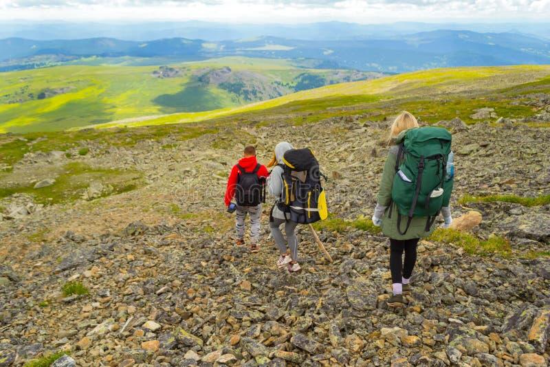 Tre turister två flickor och en pojke med ryggsäckar går ner arkivfoto