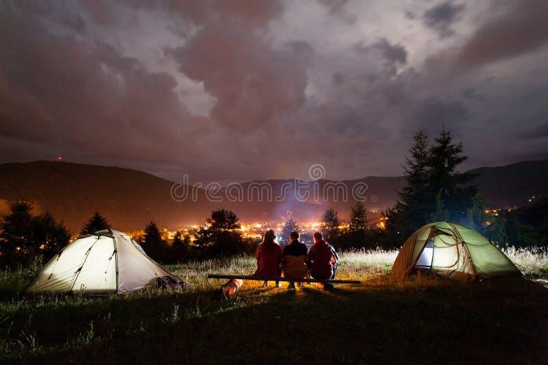 Tre turisti che si siedono sui bordi intorno al fuoco di accampamento vicino alle tende fotografia stock libera da diritti