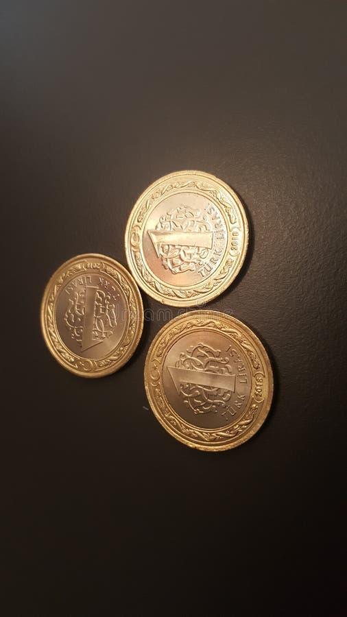 Tre 1 turkiska Lira mynt som ordnas i en triangulär geometri med något obetydligt perspektiv i slut upp bild med svart matte back arkivfoto