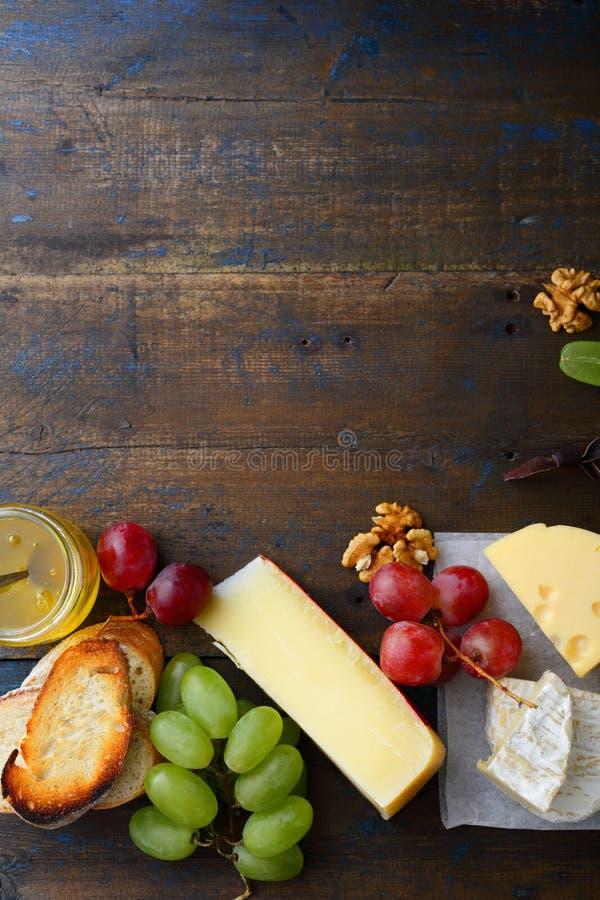Tre typer av ost med druvor, honung, bröd och valnötter Töm utrymmebakgrund royaltyfria foton