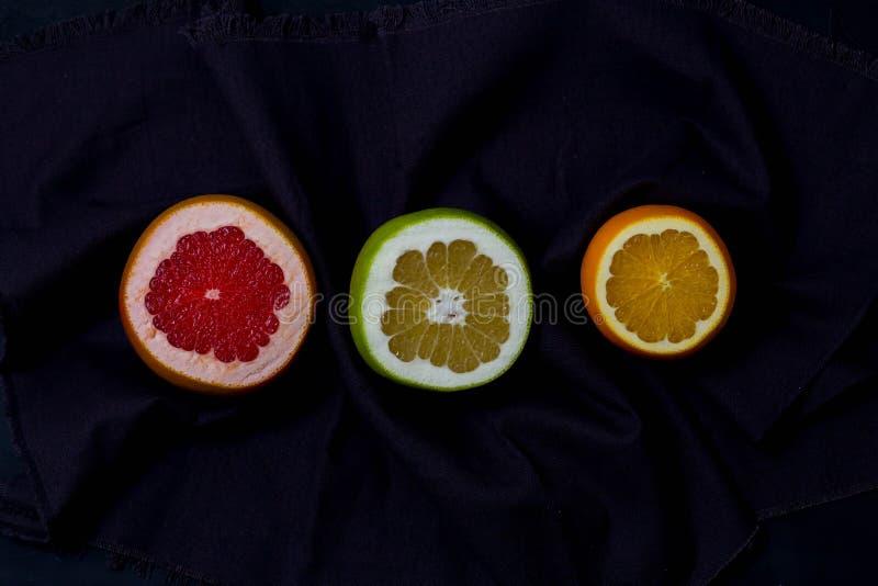 Tre typer av stycken för citrusfruktsnittrundan av orange grapefruktraringar är för att svart mörk bakgrund för blåa grå färger i arkivfoto
