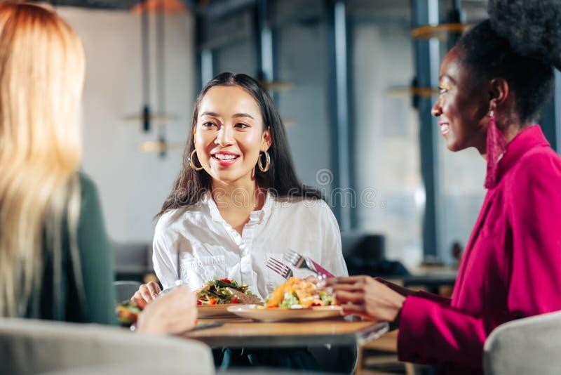 Tre unga affärskvinnor som har informellt möte i restaurang arkivbilder