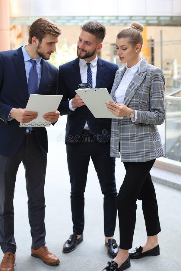 Tre unga affärsmän som står diskutera affär på ett kontorsmöte arkivfoto