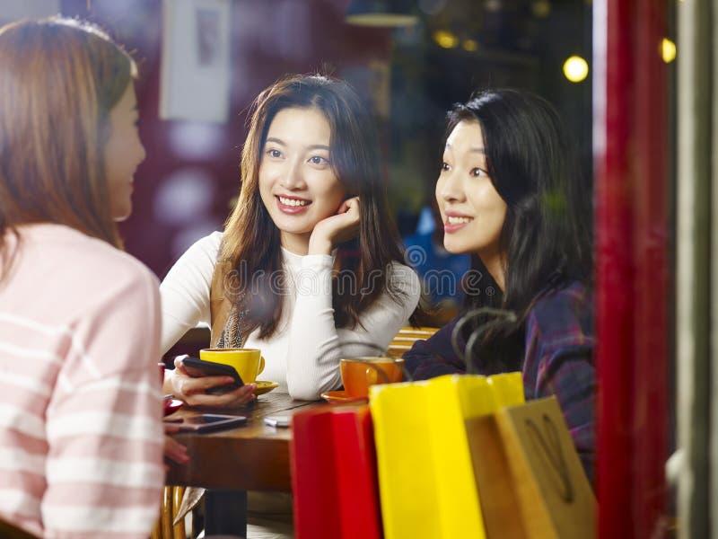 Tre unga asiatiska kvinnor som pratar samtal i coffee shop royaltyfria foton