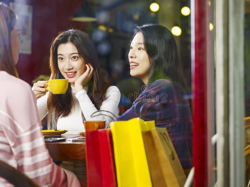 Tre unga asiatiska kvinnor som pratar samtal i coffee shop arkivbilder