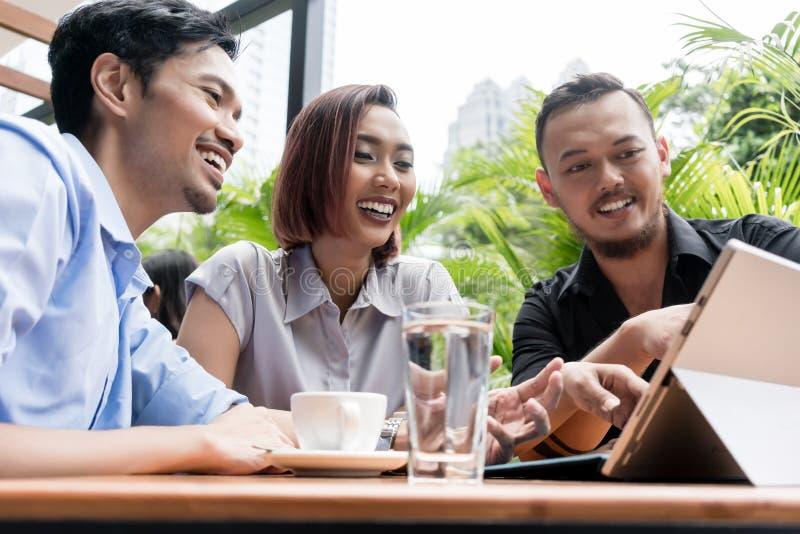 Tre unga asiatiska vänner som ler, medan genom att använda tillsammans en minnestavla royaltyfri fotografi
