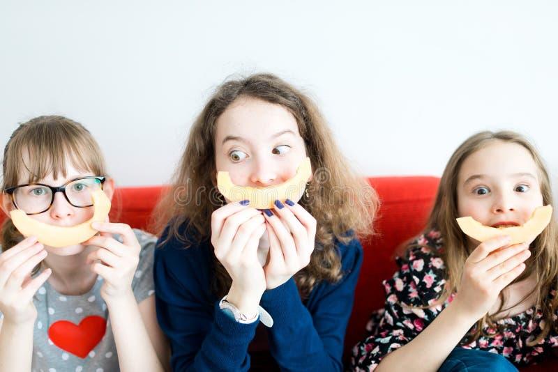 Tre unga flickor som sitter på den röda soffan och äter den gula melon royaltyfri illustrationer