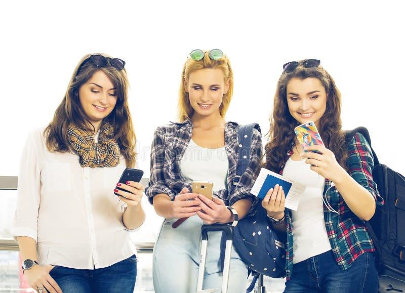 Tre unga flickor som står med bagage på flygplatsen och ser telefonen En tur med vänner arkivbilder