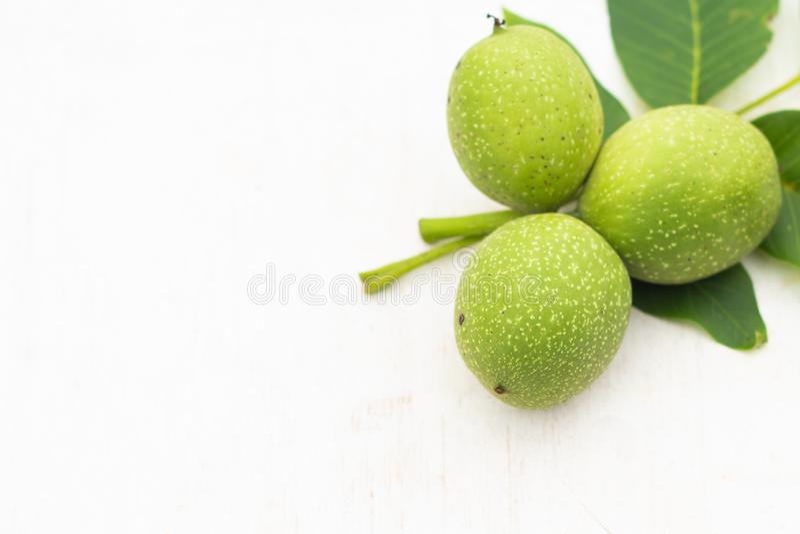 Tre unga gröna valnötter med sidor som isoleras på vit och grön bakgrund Vegetarisk mat arkivfoto