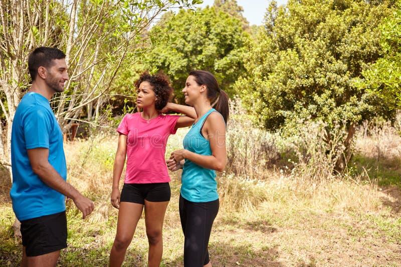 Tre unga joggers som ler på ett avbrott royaltyfri bild