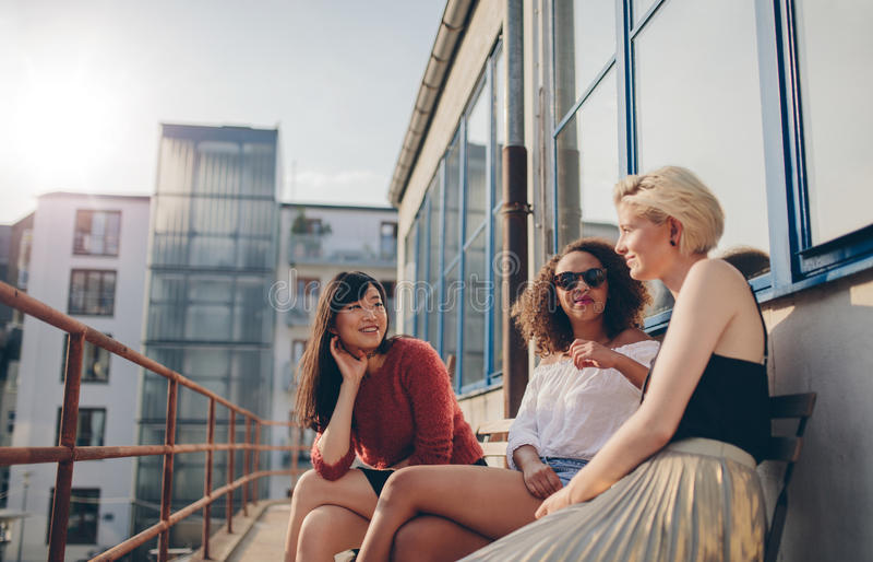 Tre unga kvinnliga vänner som sitter i balkong arkivbilder