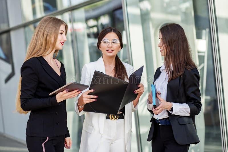 Tre unga kvinnor att diskutera planet Begrepp för affär, marknadsföring, finans, arbete, kollegor och livsstil arkivbilder