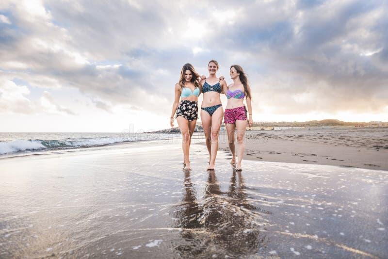 Tre unga kvinnor för gladlynta härliga damer som tillsammans går i kamratskap och har en trevlig tid semester och caucasian folk royaltyfria foton