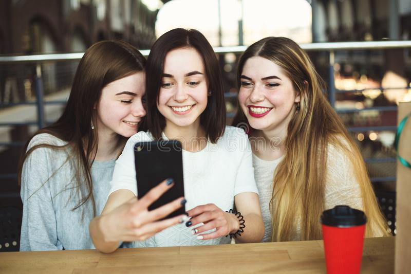 Tre unga kvinnor har gyckel och tar selfie tillsammans fotografering för bildbyråer