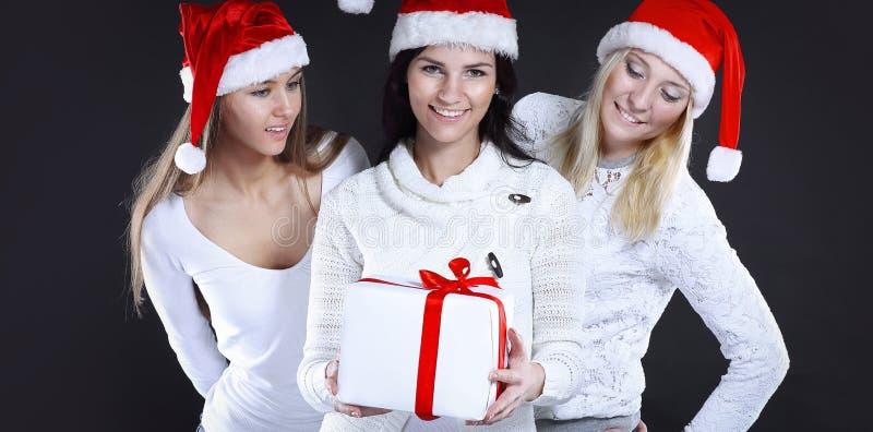 Tre unga kvinnor i dräkt av Santa Claus med julshopp royaltyfria bilder