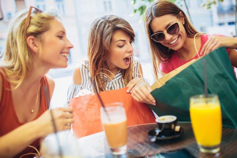 Tre unga kvinnor i ett kafé efter en shopping royaltyfria foton