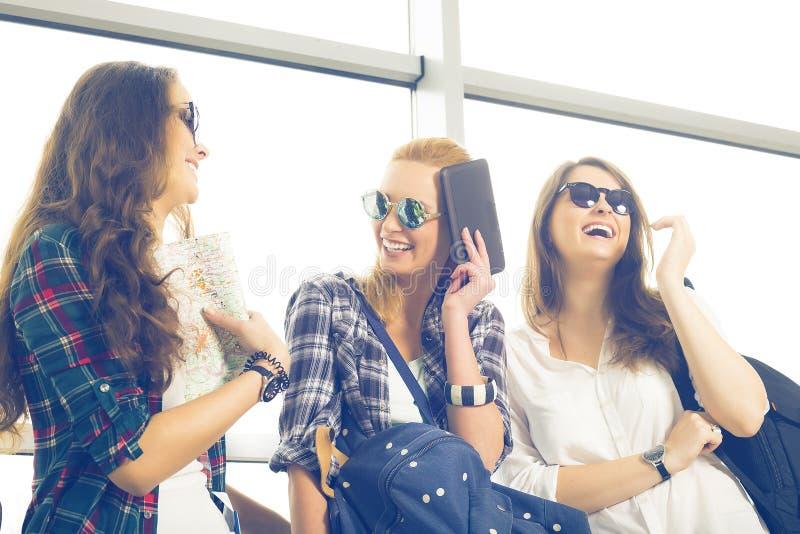 Tre unga kvinnor i solglasögon som står i flygplatsen och skrattet En tur med vänner royaltyfri foto