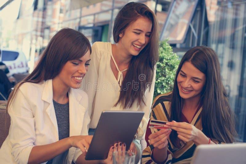 Tre unga kvinnor kontrollerar en räkning direktanslutet på kafét arkivbilder