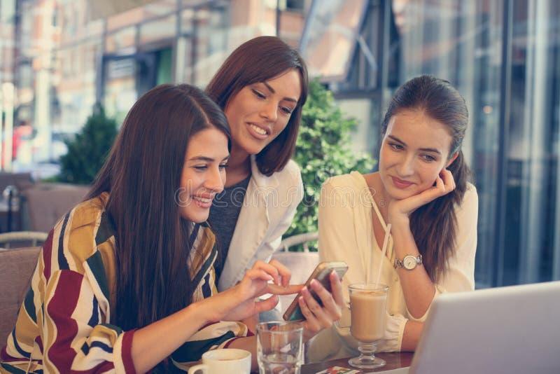 Tre unga kvinnor på kaffeavbrottet genom att använda den smarta telefonen royaltyfri foto