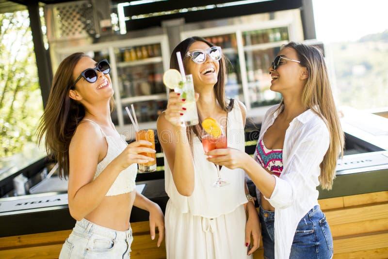 Tre unga kvinnor som dricker coctais i strandstång arkivfoto