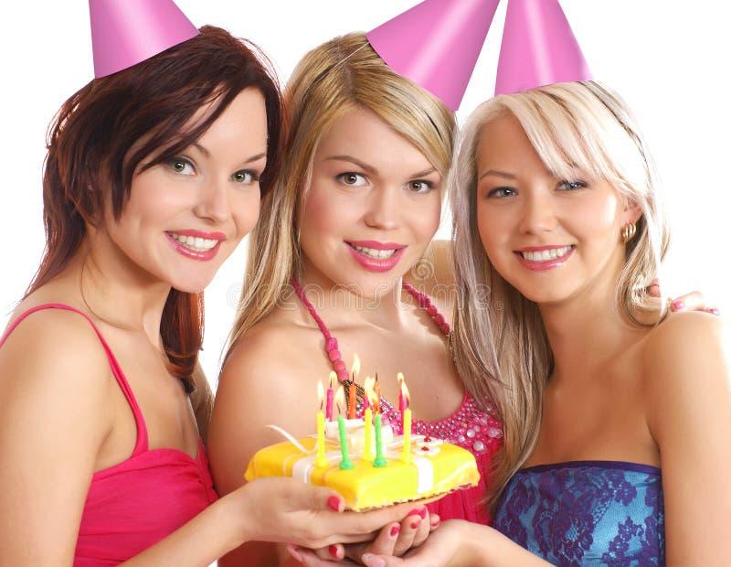 Tre unga kvinnor som firar en födelsedag royaltyfri bild