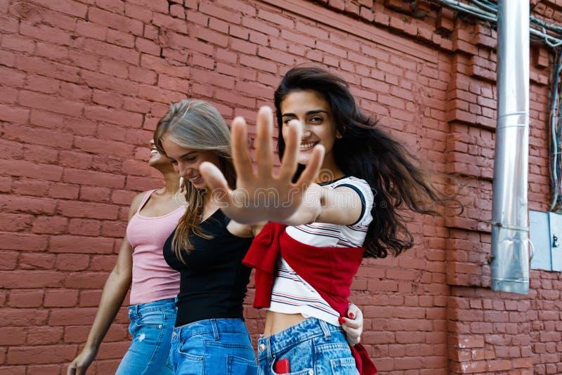 Tre unga kvinnor som går på stadsgatan royaltyfria bilder