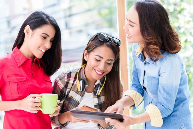 Tre unga kvinnor som har gyckel, medan se en minnestavlaPC under avbrott arkivfoto